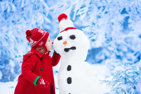 fun: Funny little toddler girl in a red knitted Nordic hat and warm coat playing with a snow man. Kids play outdoors in winter. Children having fun at Christmas time. Child building snowman at Xmas.