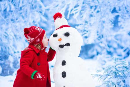 Niña divertida del niño en un rojo sombrero hecho punto nórdico y la capa caliente jugando con un hombre de nieve. Los niños juegan al aire libre en invierno. Los niños que se divierten en la época de Navidad. Muñeco de nieve del edificio del niño en Navidad.