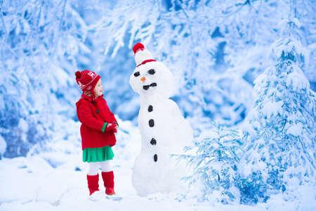 uomo rosso: Bambina divertente bambino in un rosso maglia cappello nordico e cappotto caldo a giocare con un uomo di neve. I bambini giocano all'aperto in inverno. Bambini che hanno divertimento nel periodo natalizio. Bambino edificio pupazzo di neve a Natale.