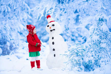 snowman: Funny little toddler girl in a red knitted Nordic hat and warm coat playing with a snow man. Kids play outdoors in winter. Children having fun at Christmas time. Child building snowman at Xmas.