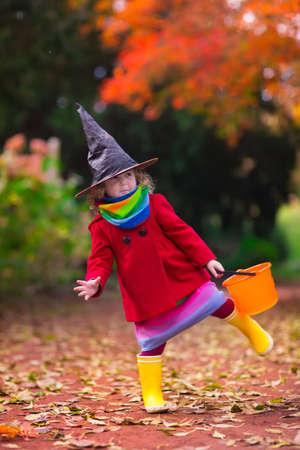 treats: Niña en traje de la bruja jugando en el parque otoño. Niño que se divierte en la baza de Halloween o tratar. Los niños truco o trato. Chico Niño con jack-o-lantern. Los niños con cubo de caramelo en el bosque de otoño. Foto de archivo