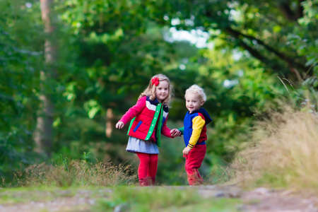 children at play: Kids playing in autumn park. Children play outdoors on a sunny fall day. Boy and girl running together hand in hand in a forest. Toddler and preschooler pick colorful oak leaf. Family fun outdoor.