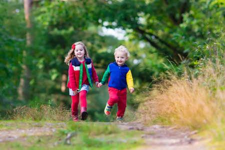 秋の公園で遊ぶ子供たち。子供の晴れた秋の日に外で遊ぶ。男の子と女の子が一緒に実行している手をつないで森の中。幼児・未就学児は、カラフ