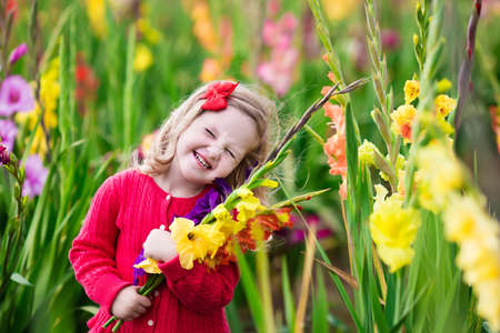 niños sonriendo: Niña que sostiene gladiolos ramo de flores. Niño recogiendo flores frescas en el jardín. Niños jardinería en otoño. Los niños juegan en el jardín que florece a finales del verano o principios del otoño. Kid descubrir la naturaleza. Foto de archivo