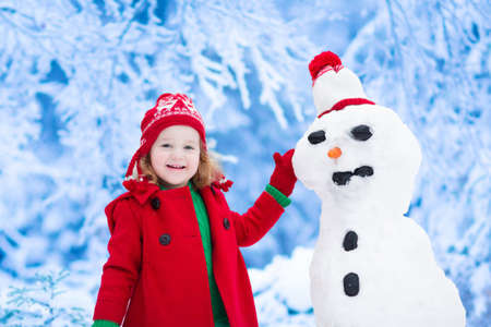 cute little girl smiling: Funny little toddler girl in a red knitted Nordic hat and warm coat playing with a snow man. Kids play outdoors in winter. Children having fun at Christmas time. Child building snowman at Xmas.