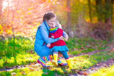 Mother and daughter play in autumn park. Parent and child walk in the forest on a sunny fall day. Children playing outdoors with yellow maple leaf. Toddler girl picking golden leaves. Mom hugging kid. Stock Photo
