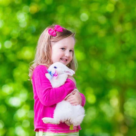 conejo: Los niños juegan con conejo real. Niño de risa en búsqueda de huevos de Pascua con el conejito blanco mascota. Pequeña muchacha del niño que juega con los animales en el jardín. Diversión del verano al aire libre para los niños con los animales domésticos.