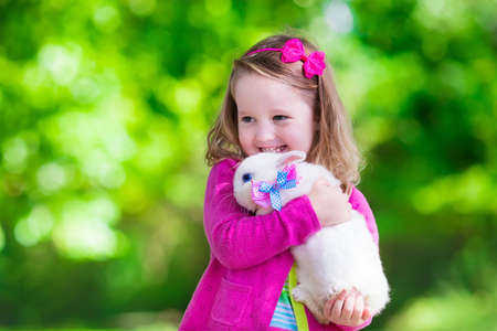 holiday pets: Children play with real rabbit. Laughing child at Easter egg hunt with white pet bunny. Little toddler girl playing with animal in the garden. Summer outdoor fun for kids with pets. Stock Photo