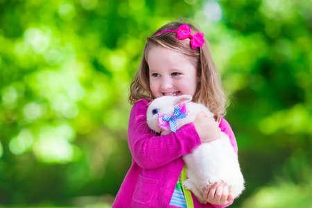 Kinder spielen mit echtem Kaninchen. Lachendes Kind auf Ostereiersuche mit weißen Haustierhäschen. Kleines Kleinkindmädchen spielt mit Tier im Garten. Sommer im Freien Spaß für Kinder mit Haustieren. Standard-Bild - 45443752
