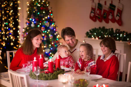decorated christmas tree: Big family with three children celebrating Christmas at home. Festive dinner at fireplace and Xmas tree. Parent and kids eating at fire place in decorated room. Child lighting advent wreath candle.