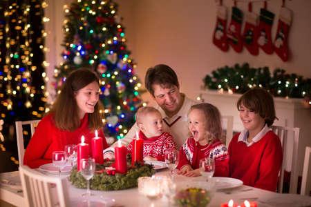 camino natale: Grande famiglia con tre bambini festeggiano il Natale a casa. Cena di gala al camino e albero di Natale. Genitori e bambini che mangiano a casa incendio nella sala decorata. Illuminazione Bambino avvento corona candela. Archivio Fotografico