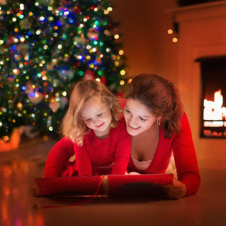 kids reading book: Mother and daughter read a book at fireplace on Christmas eve. Family with child celebrating Xmas. Decorated living room with tree, fire place and candles. Winter evening at home for parents and kids. Stock Photo