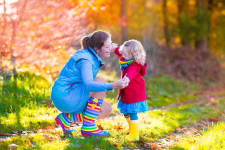 young leaves: Mother and daughter play in autumn park. Parent and child walk in the forest on a sunny fall day. Children playing outdoors with yellow maple leaf. Toddler girl picking golden leaves. Mom hugging kid. Stock Photo