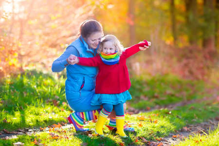 Moeder en dochter spelen in de herfst park. Ouder en kind wandelen in het bos op een zonnige herfstdag. Kinderen spelen buiten met gele maple leaf. Peutermeisje het plukken gouden bladeren. Moeder knuffelen jongen.