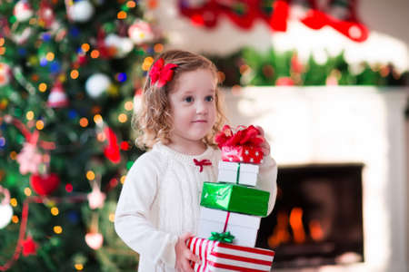 christmas morning: Family on Christmas morning at fireplace. Kids opening Xmas presents. Children under Christmas tree with gift boxes. Decorated living room with traditional fire place. Cozy warm winter day at home. Stock Photo