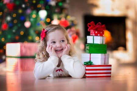 Familie op kerstochtend bij open haard. Kinderen openen Xmas presenteert. Kinderen onder de kerstboom met geschenkdozen. Ingerichte woonkamer met traditionele open haard. Gezellige warme winter dag thuis.