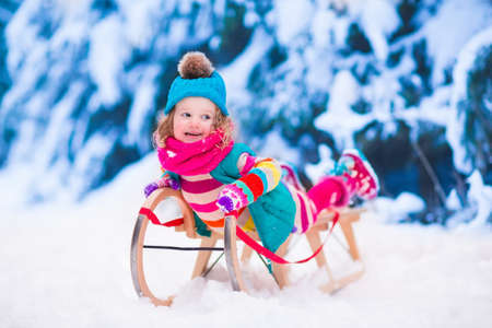 activity holiday: Little girl enjoying a sleigh ride. Child sledding. Toddler kid riding a sledge. Children play outdoors in snow. Kids sled in the Alps mountains in winter. Outdoor fun for family Christmas vacation. Stock Photo