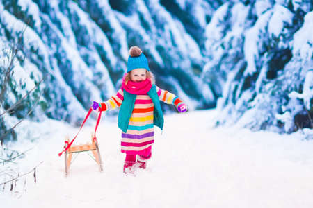 snow and trees: Little girl enjoying a sleigh ride. Child sledding. Toddler kid riding a sledge. Children play outdoors in snow. Kids sled in the Alps mountains in winter. Outdoor fun for family Christmas vacation. Stock Photo