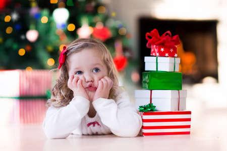Familie op Kerstmisochtend bij open haard. Kinderen openen kerstcadeautjes. Kinderen onder de kerstboom met geschenkdozen. Ingerichte woonkamer met traditionele open haard. Gezellige warme winterdag thuis. Stockfoto