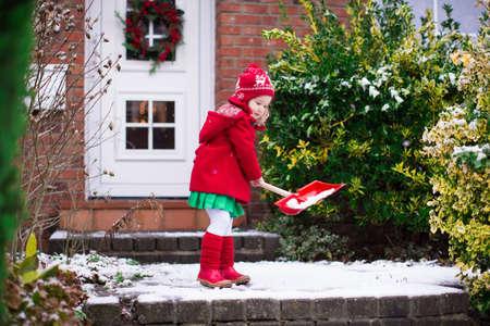 Meisje sneeuwschuiven op eigen oprit. Mooi huis versierd voor Kerstmis. Kind met schop buiten spelen in het seizoen van Kerstmis. Familie verwijderen van sneeuw tijdens de sneeuwstorm. Kinderen buiten spelen.