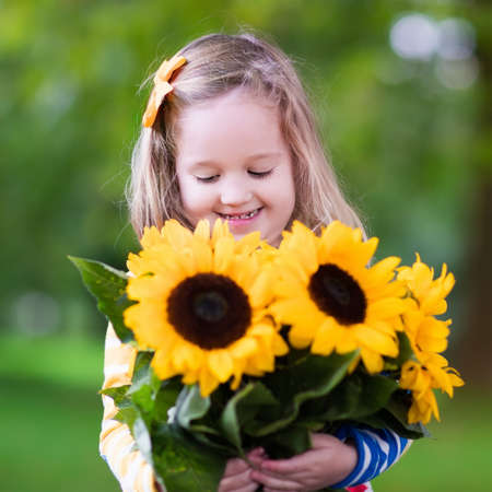 flowers sun: Happy laughing little girl holding sunflower bouquet. Child playing with sunflowers. Kids picking fresh sun flowers in the garden. Children gardening in summer. Outdoor fun for family.