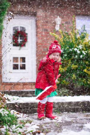 drive way: Little girl shoveling snow on home drive way. Beautiful house decorated for Christmas. Child with shovel playing outdoors in Xmas season. Family removing snow during blizzard. Kids play outside.