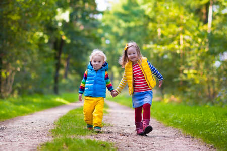 Kids playing in autumn park. Children play outdoors on a sunny fall day. Boy and girl running together hand in hand in a forest. Toddler and preschooler pick colorful oak leaf. Family fun outdoor