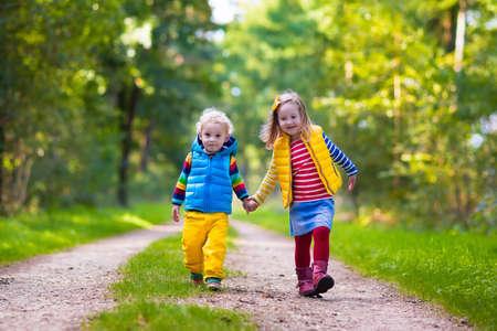 preescolar: Ni�os jugando en el parque oto�o. Los ni�os juegan al aire libre en un d�a soleado de oto�o. Ni�o y ni�a corriendo juntos de la mano en un bosque. Ni�o y preescolar recoger la hoja de roble colorido. Familia diversi�n al aire libre Foto de archivo