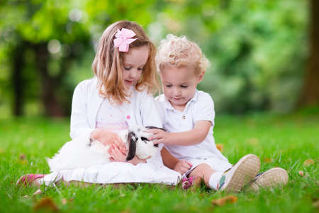 easter flowers: Children play with real rabbit. Brother and sister at Easter egg hunt with white pet bunny. Little baby boy and toddler girl playing with animal in the garden. Summer outdoor fun for kids with pets. Stock Photo