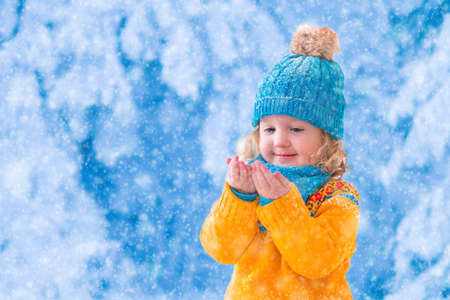 estado del tiempo: Ni�a en su�ter de punto amarillo y sombrero azul captura de los copos de nieve en el parque de invierno. Los ni�os juegan al aire libre en el bosque cubierto de nieve. Los ni�os cogen copos de nieve. Hijo del ni�o que juega afuera en la tormenta de nieve.