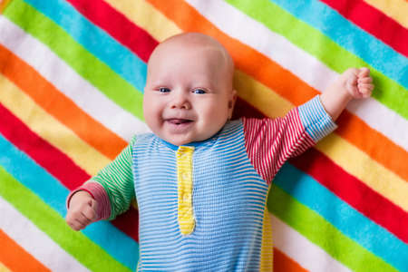 Smiling baby boy in bed. Laughing child on a colorful blanket. Children sleep. Bedding for kids. Newborn napping in bed. Healthy little new born kid shortly after birth. Clothing for kids.