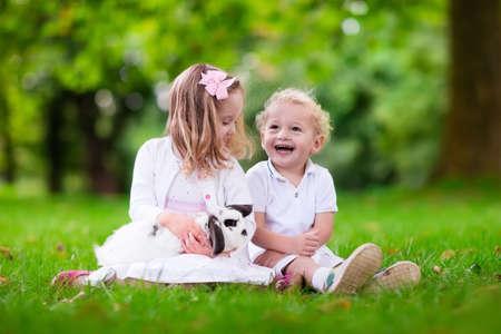 conejo: Los ni�os juegan con conejo real. Hermano y hermana en la b�squeda de huevos de Pascua con el conejito blanco mascota. Poco ni�o y ni�a ni�o que juega con los animales en el jard�n. Diversi�n del verano al aire libre para los ni�os con los animales dom�sticos.