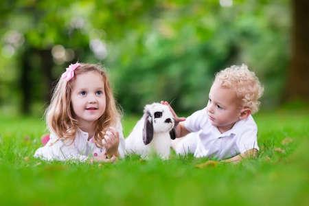 conejo: Los niños juegan con conejo real. Hermano y hermana en la búsqueda de huevos de Pascua con el conejito blanco mascota. Poco niño y niña niño que juega con los animales en el jardín. Diversión del verano al aire libre para los niños con los animales domésticos.