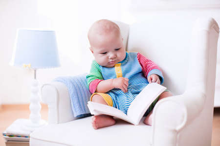 early childhood: Cute funny baby boy reading a book sitting in a white chair at home. Children read books in a library seat. Nursery and playroom interior for kids. Early development and learning for young kid.