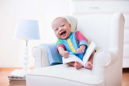 boy room: Cute funny baby boy reading a book sitting in a white chair at home. Children read books in a library seat. Nursery and playroom interior for kids. Early development and learning for young kid.
