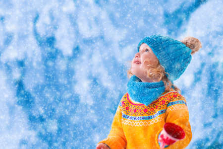young people fun: Little girl in yellow knitted sweater and blue hat catching snowflakes in winter park. Kids play outdoor in snowy forest. Children catch snow flakes. Toddler kid playing outside in snow storm.