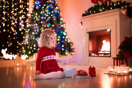 happy family at home: Family on Christmas eve at fireplace. Kids opening Xmas presents. Children under Christmas tree with gift boxes. Decorated living room with traditional fire place. Cozy warm winter evening at home. Stock Photo