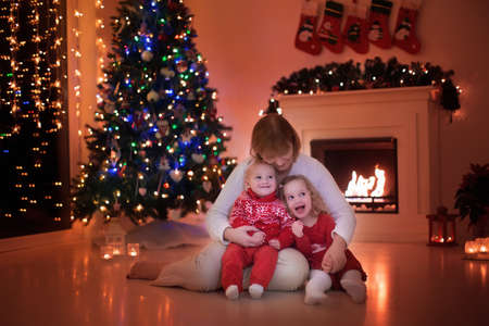 place for children: Mother and children read a book at fireplace on Christmas eve. Family with child celebrating Xmas. Decorated living room with tree, fire place and candles. Winter evening at home for parents and kids.