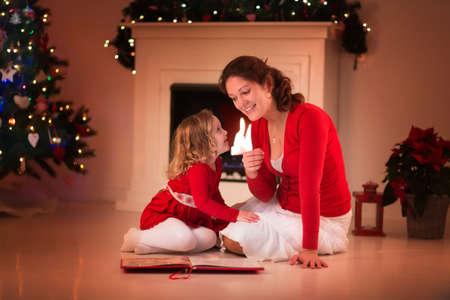 niñas pequeñas: Madre e hija leer un libro en la chimenea en la víspera de Navidad. En familia con niño celebración de Navidad. Sala de estar decorada con el árbol, chimenea y velas. Noche de invierno en el hogar para los padres y niños.