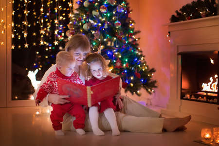 Mother and children read a book at fireplace on Christmas eve. Family with child celebrating Xmas. Decorated living room with tree, fire place and candles. Winter evening at home for parents and kids.