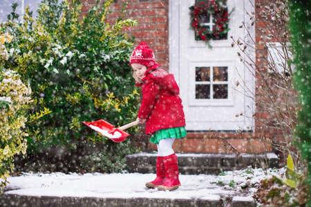 haushaltshilfe: Kleines M�dchen, das Schneeschaufeln auf Home Auffahrt. Sch�nes Haus f�r Weihnachten dekoriert. Kind mit Schaufel im Freien spielen in Weihnachtssaison. Familie, der Schnee w�hrend Schneesturm. Kinder spielen drau�en.