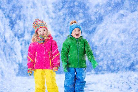 gemelos ni�o y ni�a: Ni�a y ni�o en colores sombrero captura de los copos de nieve en el Parque de invierno en la v�spera de Navidad. Vacaciones Esqu� para familias con ni�os. Los ni�os juegan al aire libre en el bosque cubierto de nieve. Los ni�os cogen escama de la nieve en Navidad.