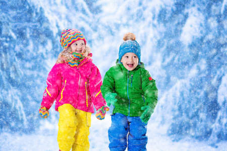 sweater girl: Little girl and boy in colorful hat catching snowflakes in winter park on Christmas eve. Ski vacation for family with children. Kids play outdoor in snowy forest. Children catch snow flake on Xmas. Stock Photo