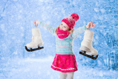 楽しんで満足して笑う少女雪の公園でスケート。冬のスポーツと子供と家族のためのクリスマス休暇にアウトドア。雪で遊んで面白い子供。子供は 写真素材