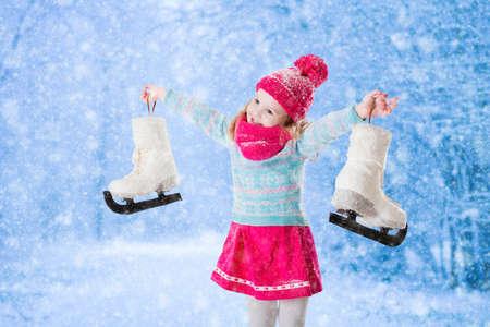 Gelukkig lachend meisje plezier schaatsen in de besneeuwde park. Wintersport en outdoor activiteiten voor het gezin met kinderen op de kerstvakantie. Grappig kind spelen met sneeuw. Kind bedrijf schaatsen.