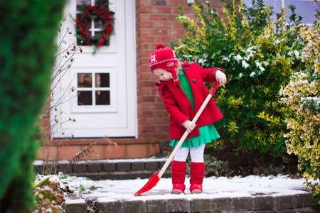 trabajando en casa: Ni�a palear nieve en camino de entrada a casa. Hermosa casa decorada para la Navidad. Ni�o con la pala de jugar al aire libre en la temporada de Navidad. Familia quitar nieve durante la ventisca. Los ni�os juegan afuera.