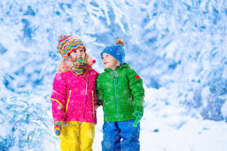 jungle boy: Little girl and boy in colorful hat catching snowflakes in winter park on Christmas eve. Ski vacation for family with children. Kids play outdoor in snowy forest. Children catch snow flake on Xmas. Stock Photo