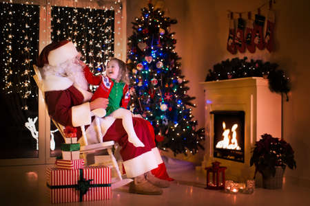 baby open present: Child and Santa Claus in rocking chair at fireplace on Christmas eve. Family celebrating Xmas. Decorated living room with tree, gifts, fire place, candles. Winter evening at home for parents and kids.