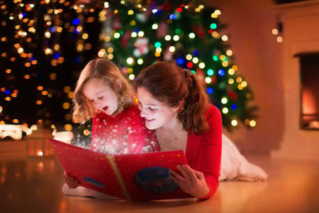 books new books: Mother and daughter read a book at fireplace on Christmas eve. Family with child celebrating Xmas. Decorated living room with tree, fire place and candles. Winter evening at home for parents and kids. Stock Photo