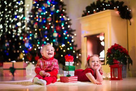 Familie op kerstavond bij open haard. Kinderen openen kerstcadeautjes. Kinderen onder de kerstboom met geschenkdozen. Ingerichte woonkamer met traditionele open haard. Gezellige warme winteravond thuis.